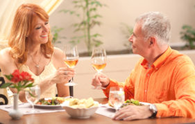Mature couple at table in a brightly lit restaurant, raising glasses of white wine for a toast. She is wearing a strappy cream dress and he has a bright orange shirt.