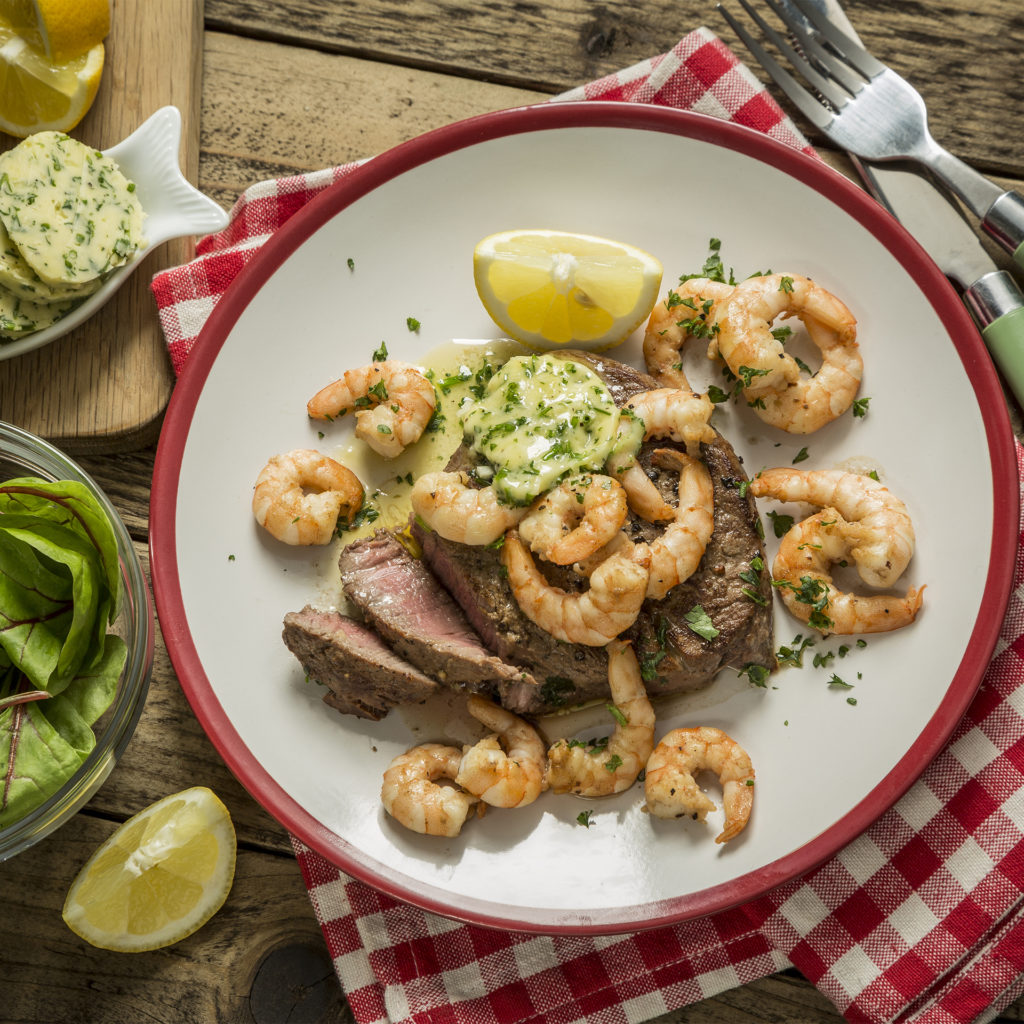 Surf and Turf steak with prawns, melting herby butter and lemon wedge