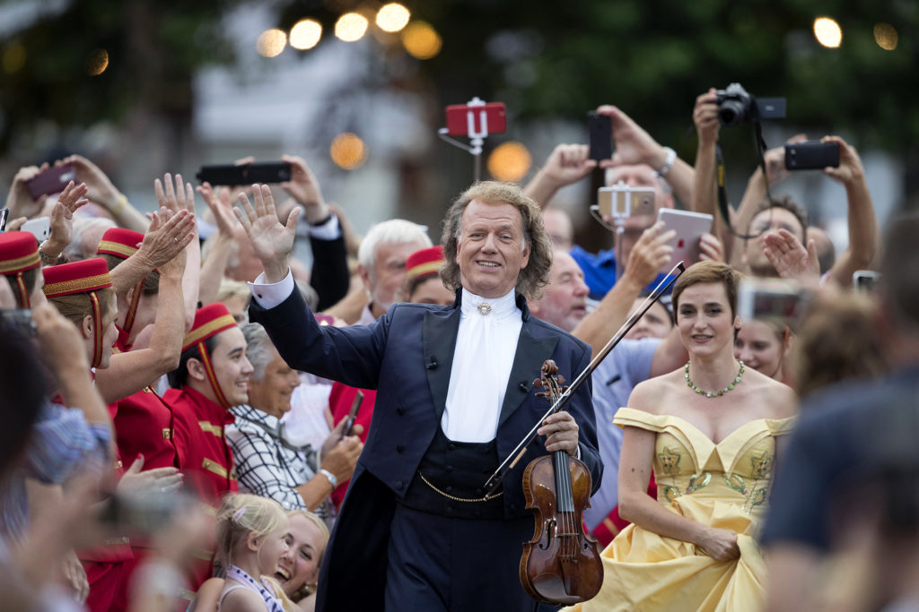 Andre Rieu surrounded by cast members of show