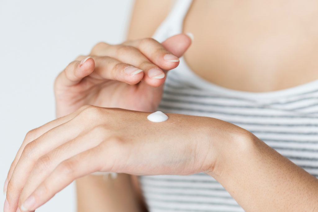 Woman rubbing cream on the back of her hand