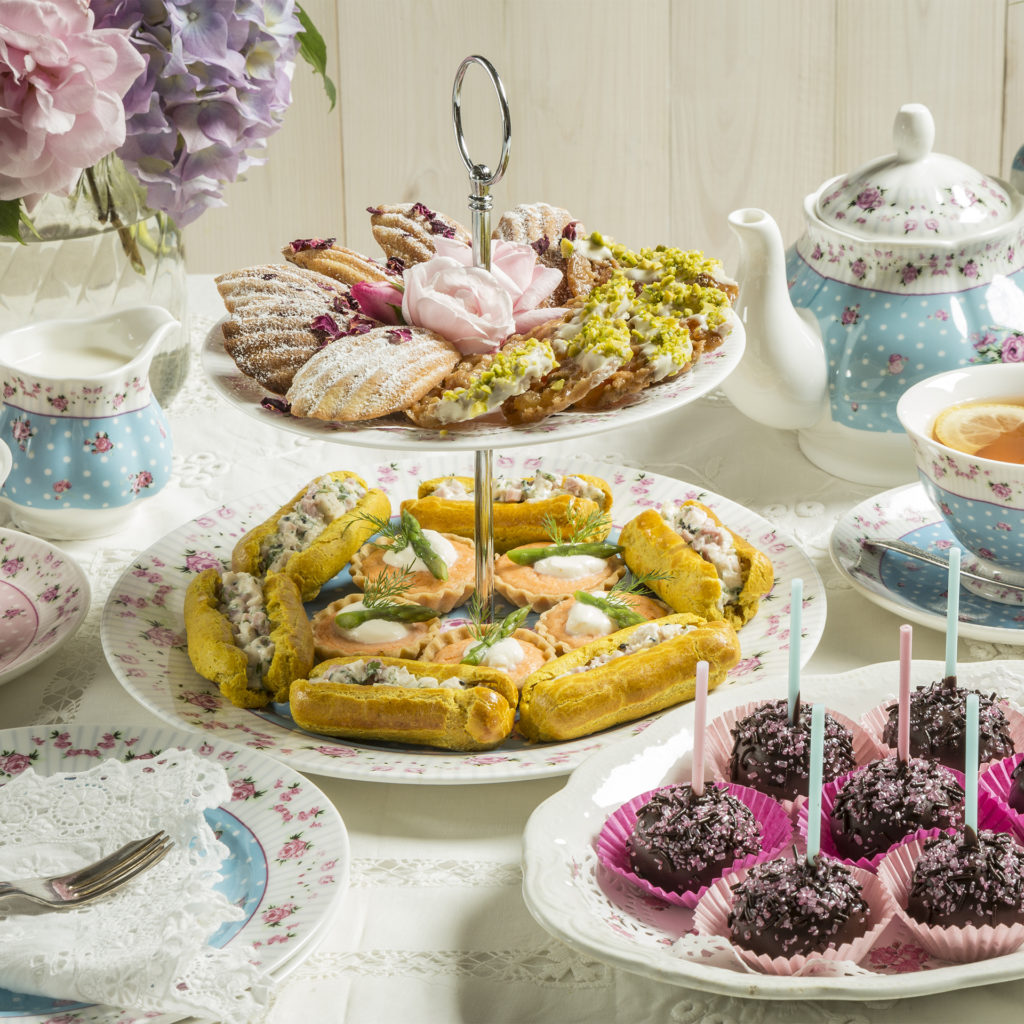 Table set for afternoon tea, with china cake stand laden with mini eclairs, quiches, biscuits and cake pops, recipes in My Weekly latest issue
