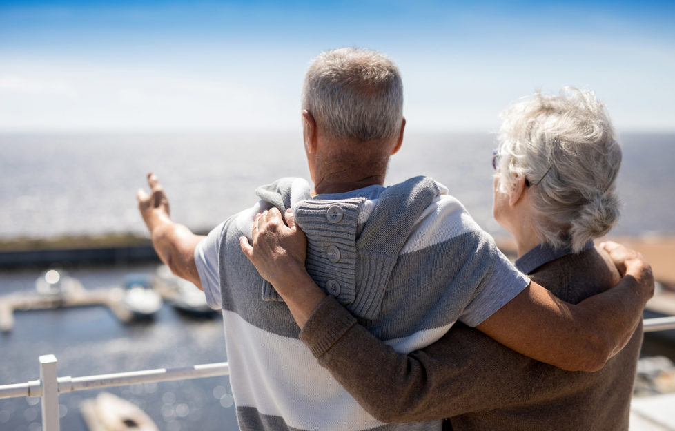 Senior man pointing at beach while embracing his wife by seaside
