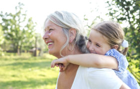 Grandmother and granddaughter playing outdoors.