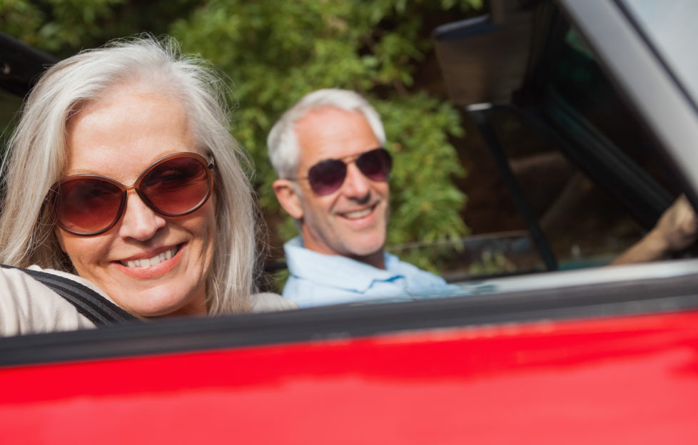 Side view of cheerful mature couple driving red cabriolet on sunny day