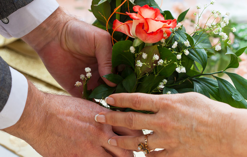 Older man giving a bouquet of roses to a woman Pic: Istockphoto