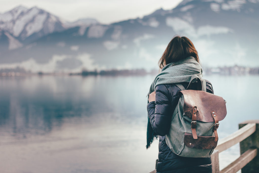 Hipster young girl with backpack enjoying landscape standing near the lake.