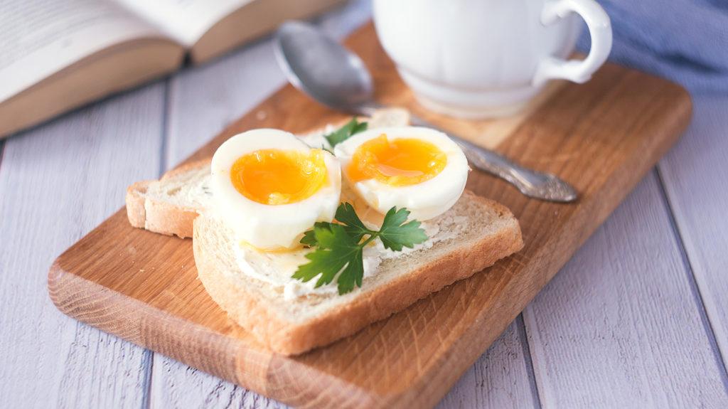 freshly boiled white egg on wooden board. Healthy fitness breakfast.