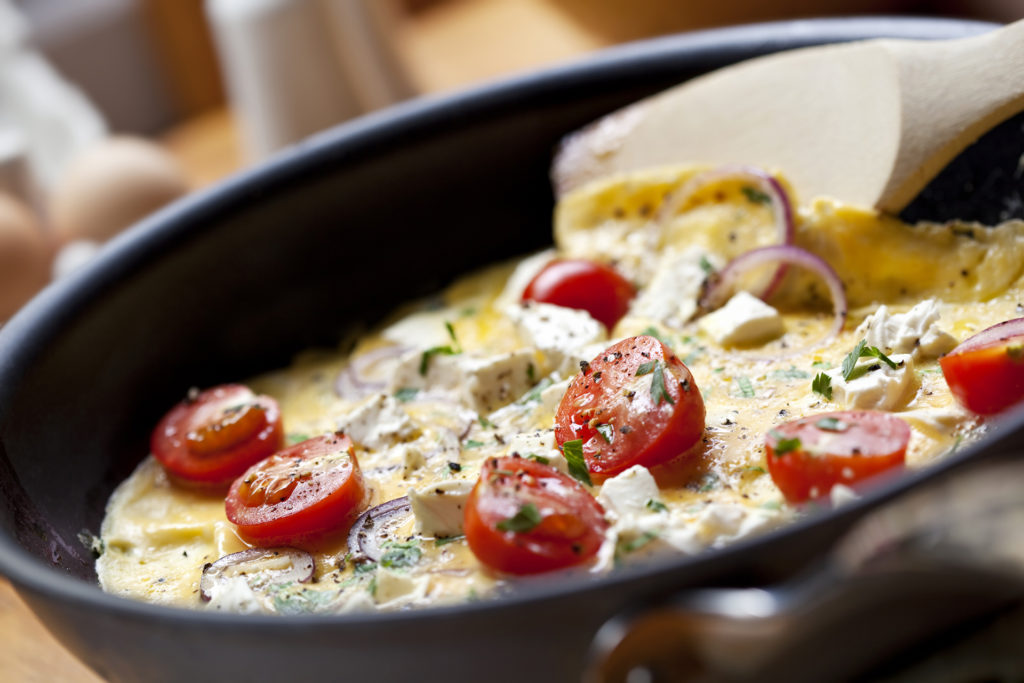 Cooking omelet in a pan, ready to serve. With Cherry tomatoes,
