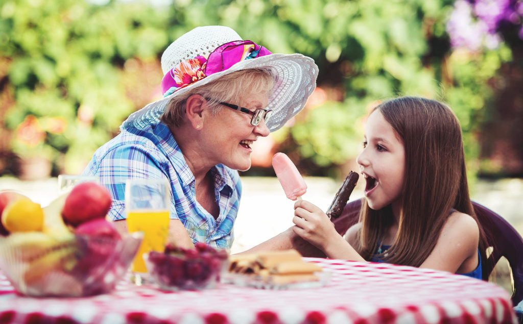Happy little girl and her grandmother eating ice cream, having fun together in the garden.