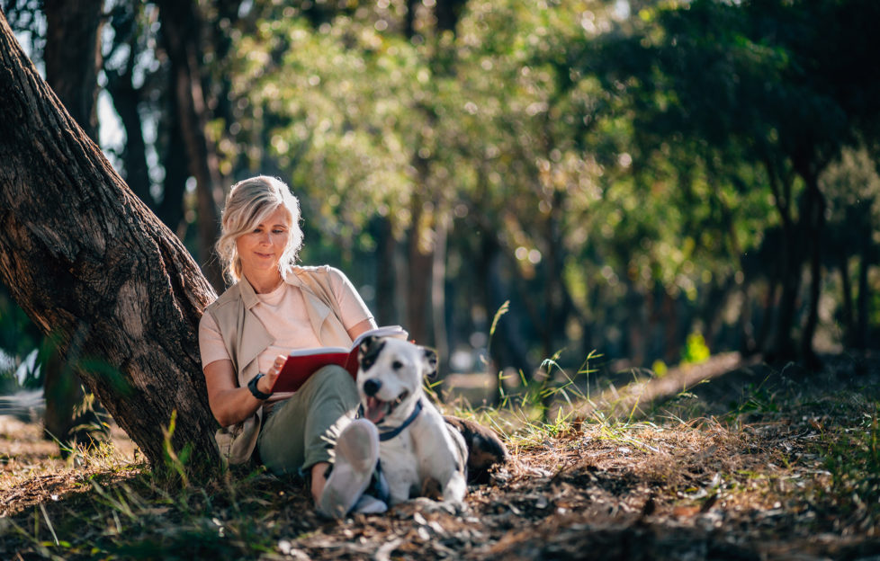 Happy mature woman with dog sitting under forest tree and reading book in the woods