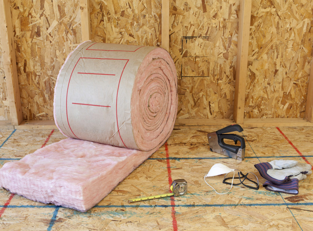 roll of insulation material on a chipboard floor, tools, gloves and mask nearby