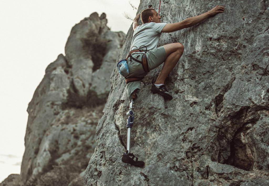 Man with space tech prosthetic leg free-climbing a rock face