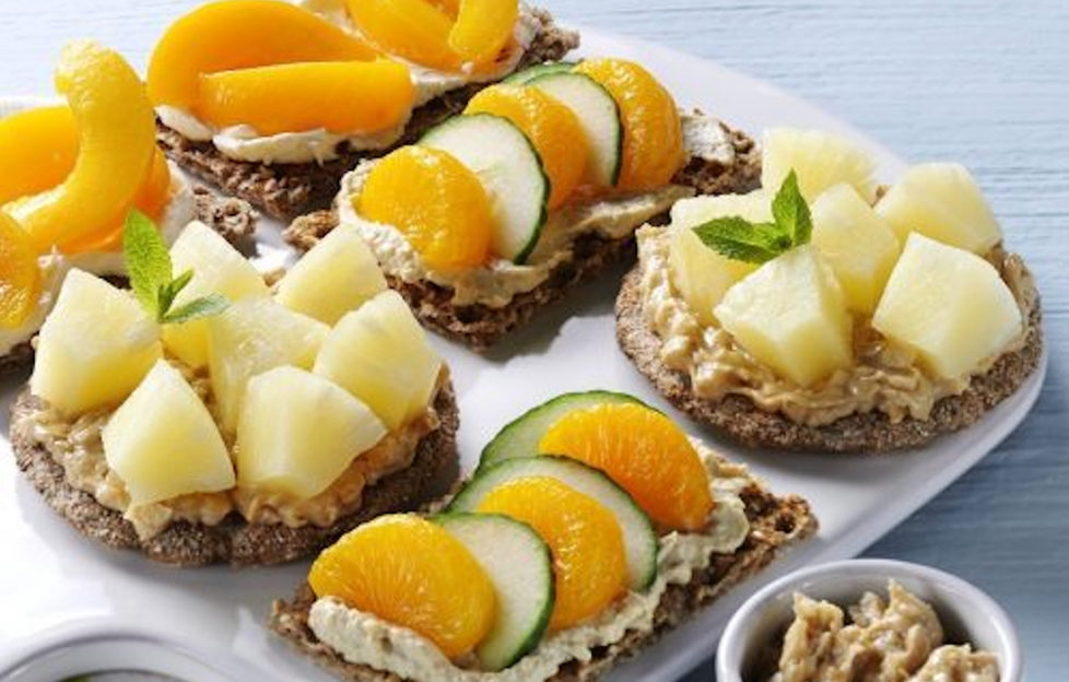 A variety of crispbread toppings with canned peach, mandarin and pineapple