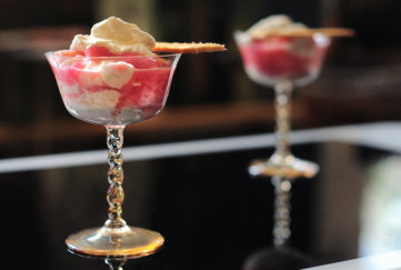 rhubarb fool in delicate stemmed glass dishes, dark background