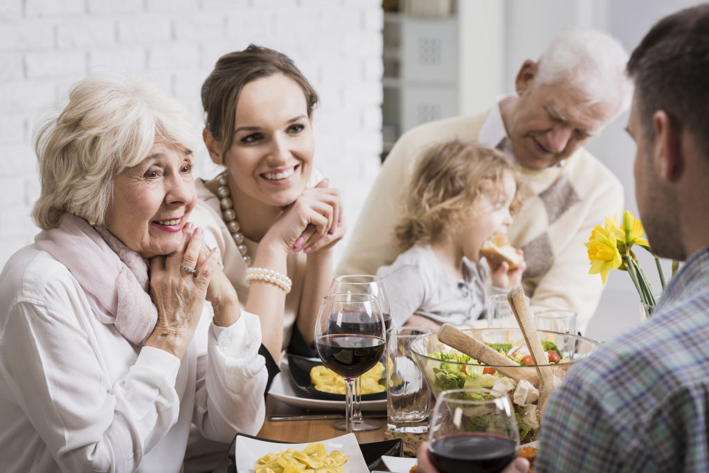 Family at dinner table - grandparents, parents and children
