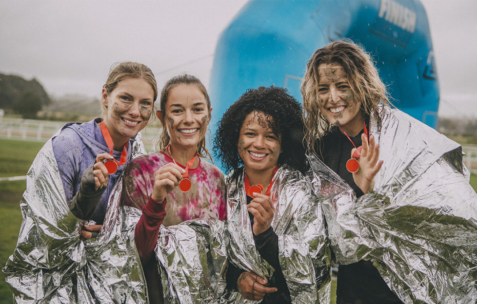 Four women are posing for the camera in foil blankets with the medals they have won from completing a charity obstacle course.