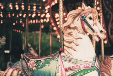 Carousel horse with green saddle, decorated with roses