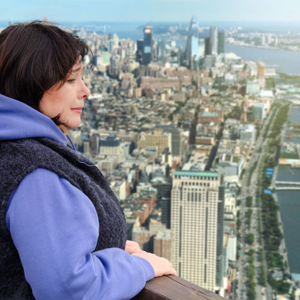 Woman afraid of heights grips handrail and looks out over city from high viewpoint