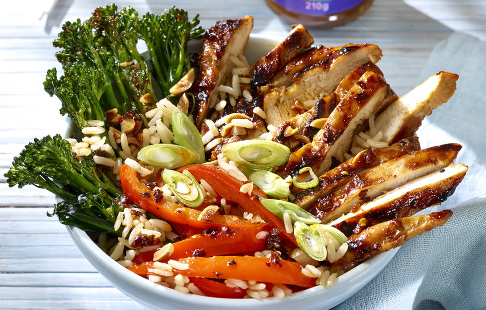 Sliced chicken with dark glaze, broccoli, red peppers, rice and spring onions arranged in groups in a bowl