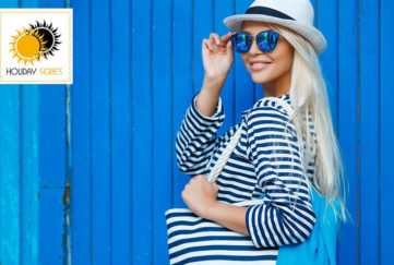 Woman in navy/white striped top and big sunhat against blue painted wooden shed, adjusting sunglasses, looking flirty