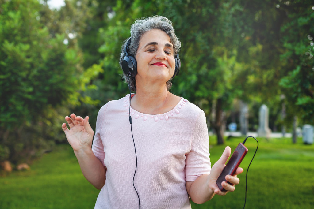 Senior woman listening music with headphones in the park