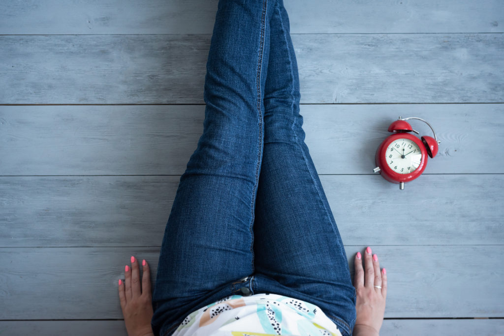 Tired woman and red alarm clock on a wooden floor background.