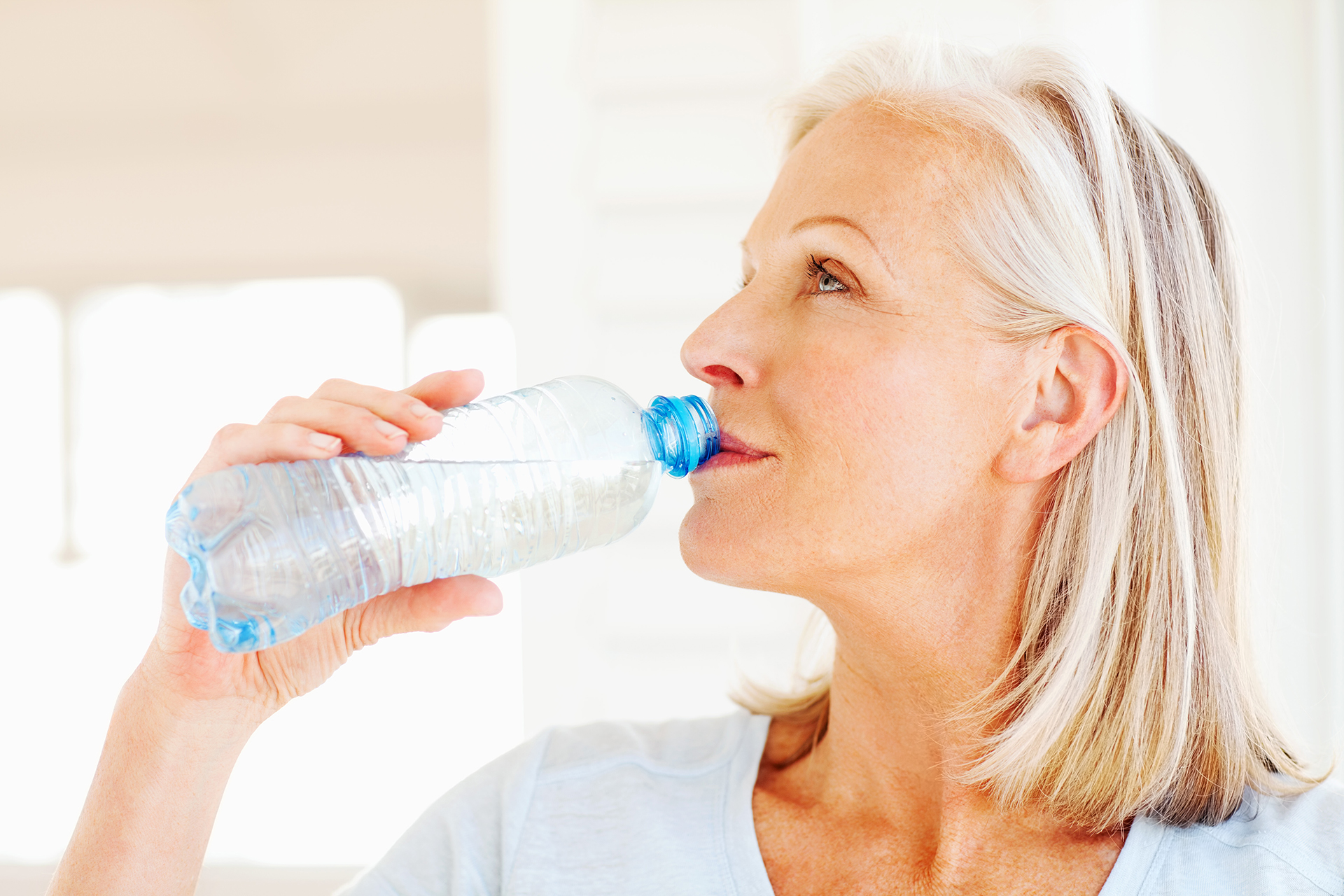 Senior woman drinking from a water bottle