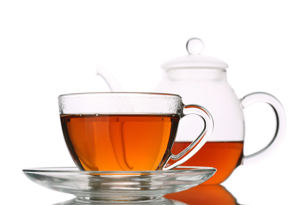 Clear cup and tea pot full of black tea