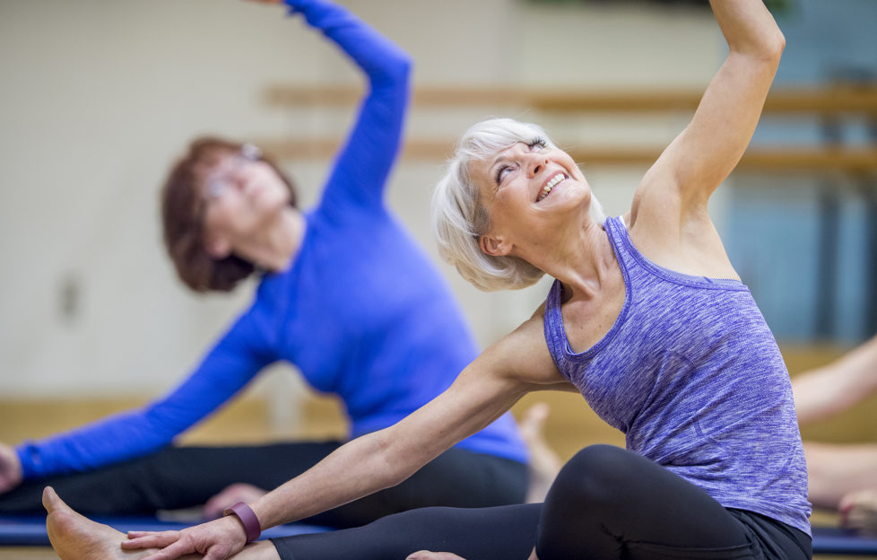 Two Caucasian women are indoors in a health center. They are wearing casual athletic clothing. They are sitting on the floor and reaching their arms into the air.