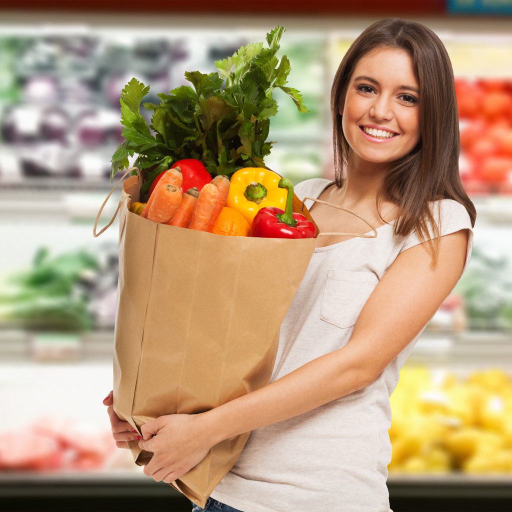 Smiling woman in supermarket holding paper bag full of unwrapped vegetables