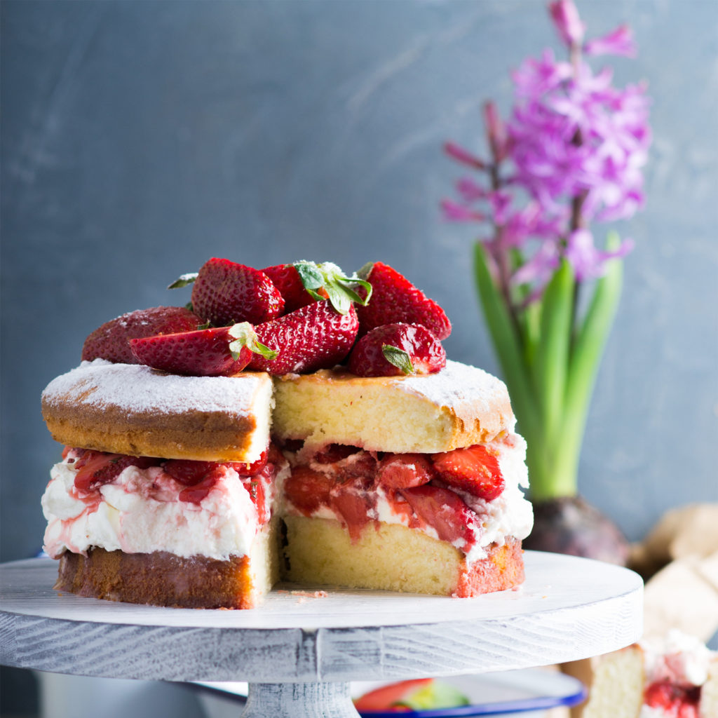 Victoria sponge cake topped and filled with fresh strawberries for My Weekly Bake Off quiz