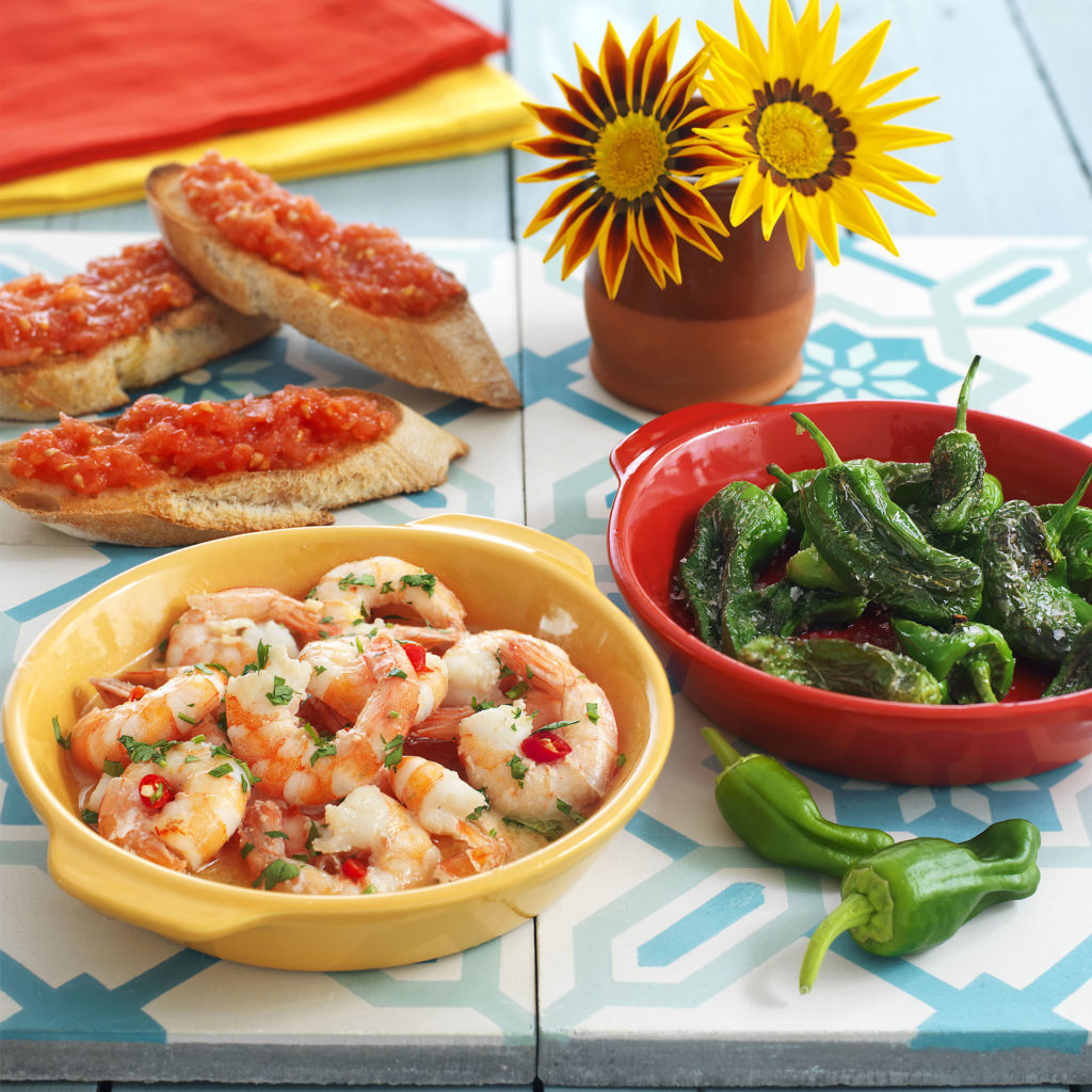 Bright coloured bowls of tapas, green peppers, prawns and tomato bread with yellow flowers in a vase