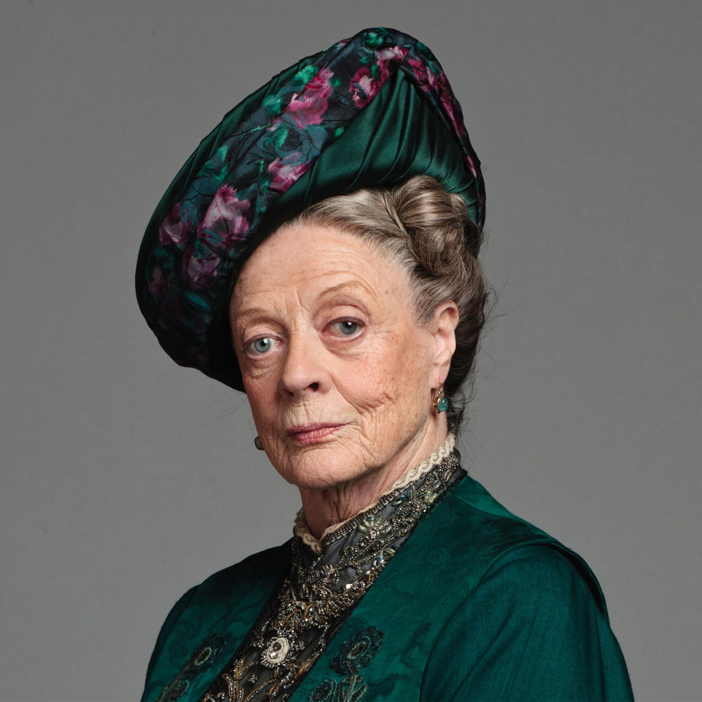 Portrait of Dame Maggie Smith as Dowager Countess Violet, one eyebrow raised sardonically, in teal green silk jacket and hat with purple decoration