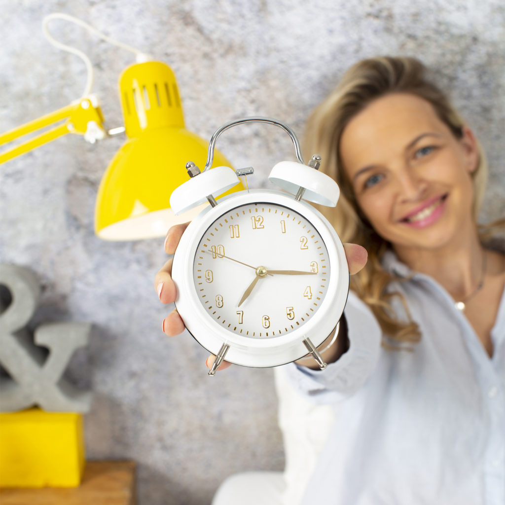 Smiling woman holding out old fashioned alarm clock, time is 7.20am