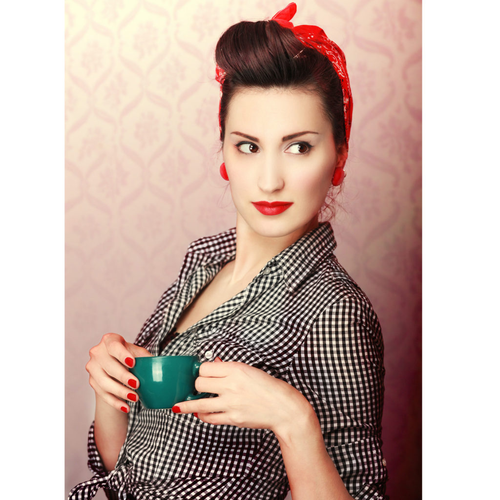Woman dressed as 1940s factory girl with overall, headscarf and red lipstick, holding teacup and looking over her shoulder