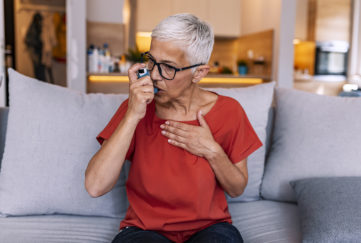 Mature woman, short grey hair, red top, takes inhaler sitting on sofa