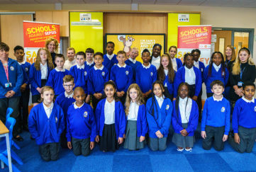 Class of pupils pose in front of sepsis awareness display
