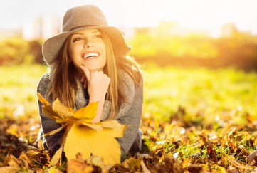 Go sober for October and feel great! Happy woman lying on stomach in autumn park, holding golden leaves, wearing floppy hat