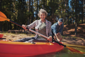 Portrait of happy senior woman in a kayak holding paddles. Woman canoeing with man in background at the lake.