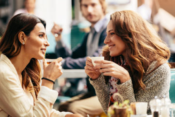 Two friends talking and drinking coffee.
