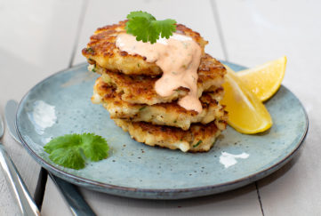 Phil Vickery recipe. Stack of 4 squid and prawn patties on a grey-blue plate, garnished with a drizzle of dip, parsley sprigs and lemon wedges