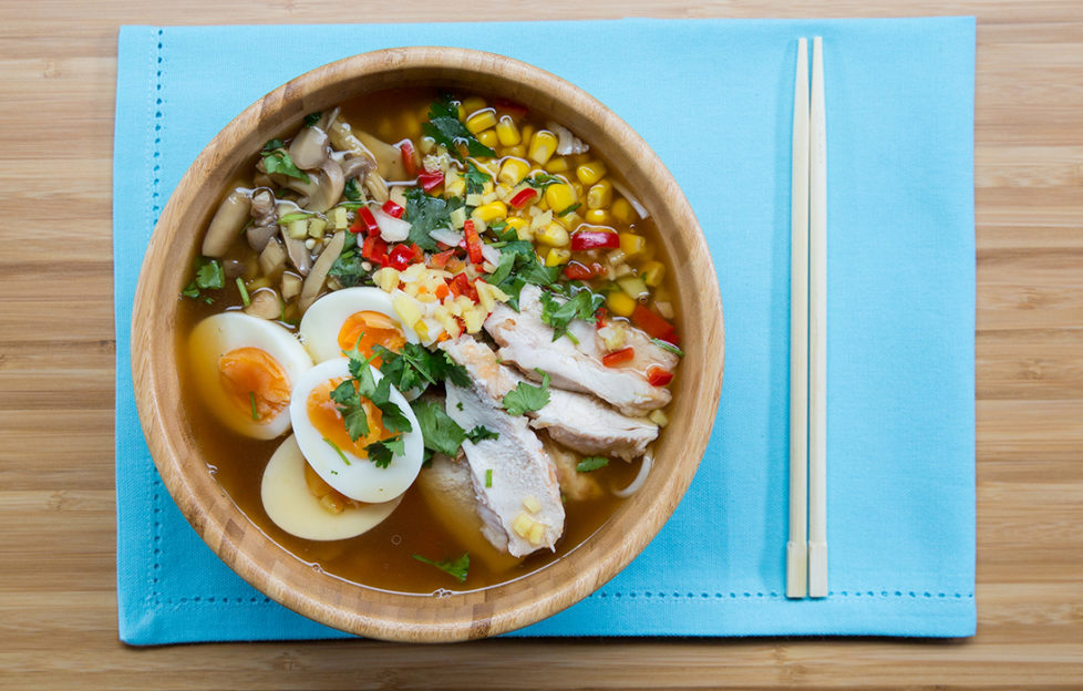 Bowl of chicken ramen noodles with halved boiled egg, sweetcorn and fresh coriander garnish