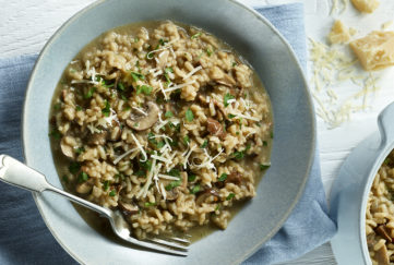Bowl of rich brown mushroom risotto garnished with grated cheese and chopped parsley