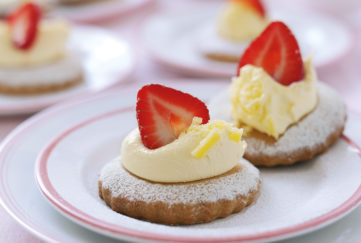 Small plate with two round shortcake biscuits, each decorated with whipped cream and half a strawberry
