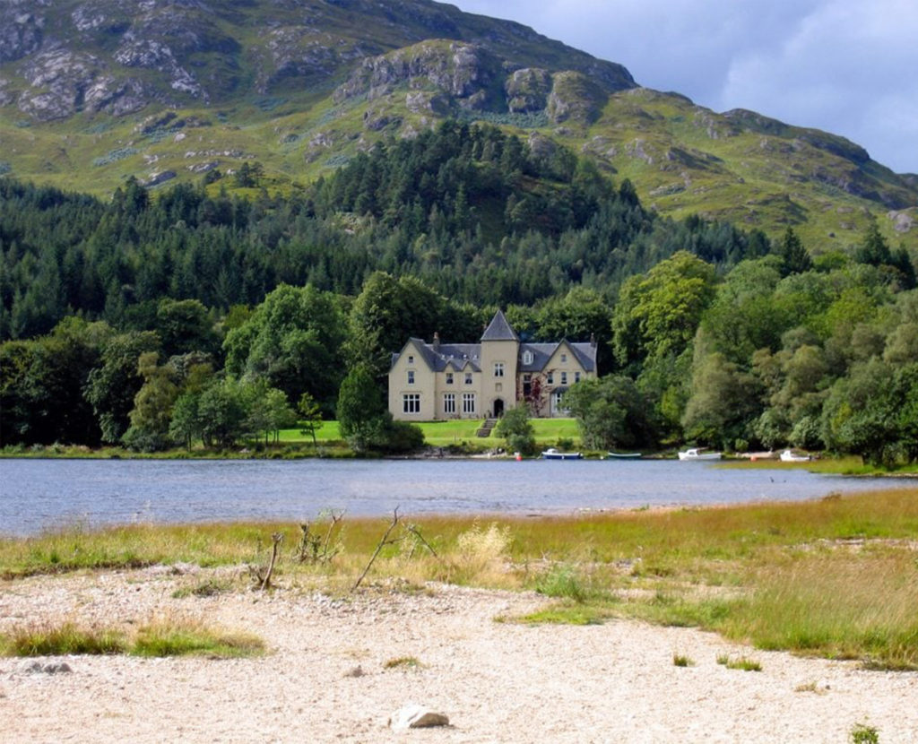 Large, grand house with tower amid trees with mountains behind, loch in foreground