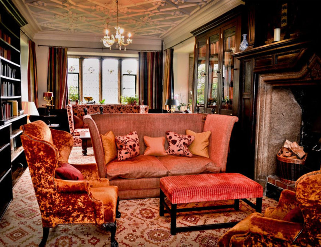 Orange silk and velvet chairs and sofa, long dark wood bookshelves, huge stone fireplace, mullioned window at end and low ornate ceiling