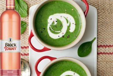 wine with soup - two bowls of rich green soup with a swirl of cream, and a bottle of rose wine