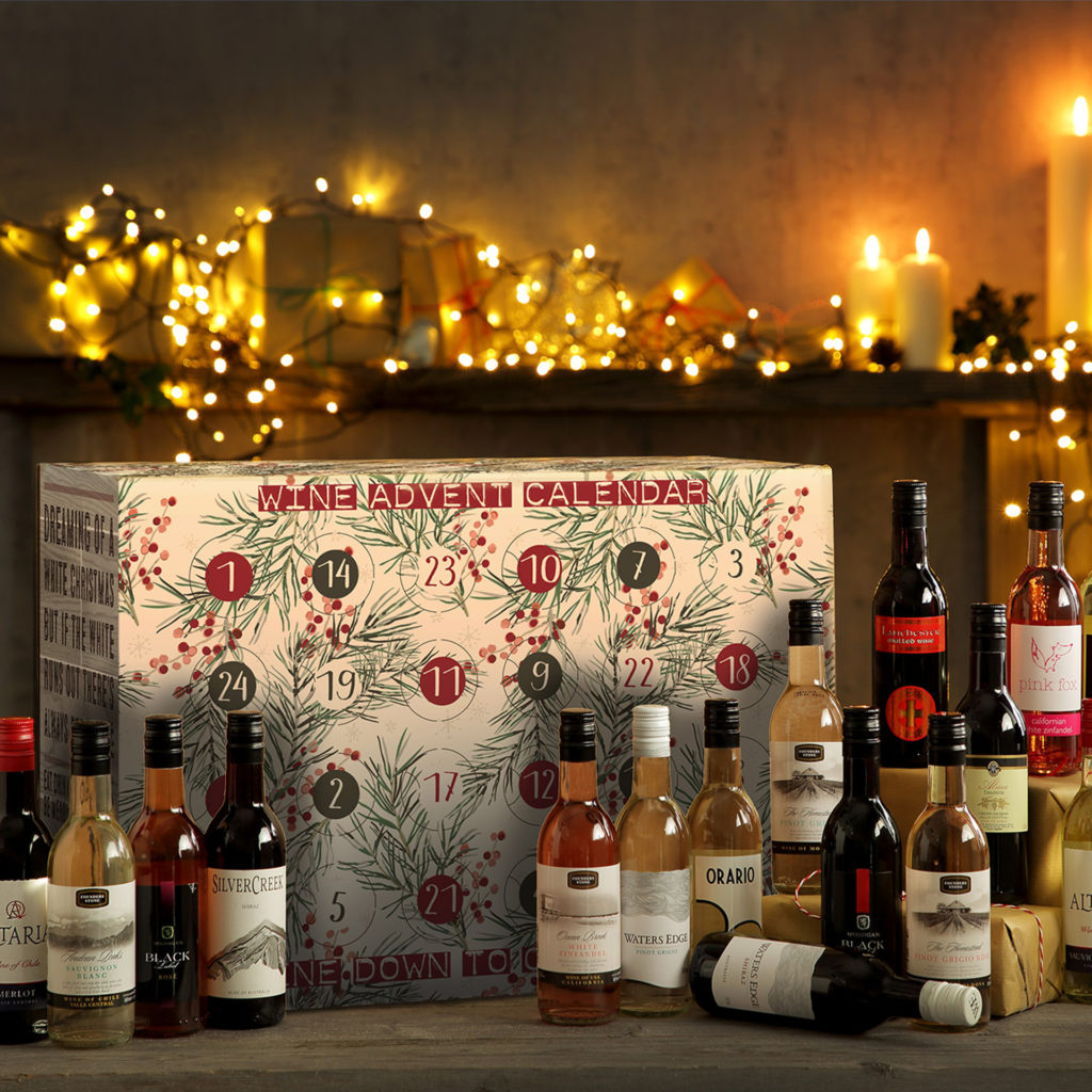 Wine advent calendar, box with numbered doors, array of miniature bottles, fairy lights behind. featured in My Weekly latest issue