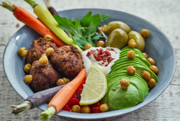 Plant power winter bowl with different coloured baby carrots, golden falafels, green rocket and avocado, red peppers, roasted chickpeas and dollop of Alpro soya yogurt swirled with red harissa paste