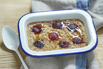 Rectangular enamel dish containing oats studded with cherries and drizzled with maple syrup
